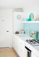 Pale blue tiled splashback and open shelf in bright kitchen