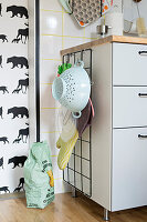 Wire mesh for hanging kitchen utensils on end of cabinet