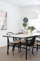 Various black chairs around simple dining table