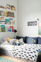 Books arranged on narrow shelves above bed in child's bedroom