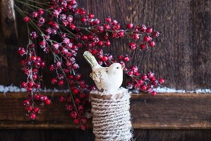 Christmas arrangement of bird ornament and branches of berries