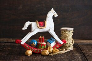 Christmas arrangement of small wooden rocking horse and walnuts
