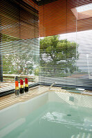 Louvre blinds on glass walls screening jacuzzi