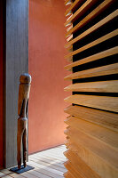 Wooden sculpture against wall and walls with different surfaces