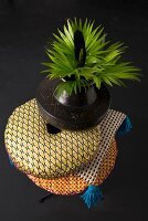 Bunt gemusterter Kissenstapel mit Ethno-Vase und grünen Blättern