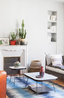 Two retro coffee tables on blue patterned rug in front of disused fireplace