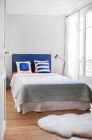 View through open door into bright bedroom in period apartment