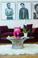 Round coffee table on sheepskin rug in front of purple sofa and pictures