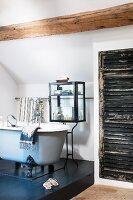 Free-standing, vintage-style bathtub on black platform in front of bath utensils in glass case