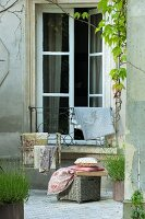 Cushions and fabrics on wicker trunk and valet stand in courtyard in front of French windows