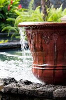 Overflowing ceramic pot in pool