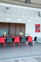 Black and red chairs around dining table in open-plan kitchen