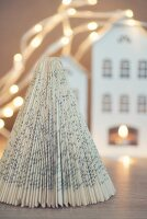 Christmas tree made from folded book pages in front of house-shaped lantern