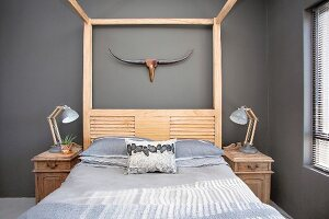 Wood-framed bed and bedside cabinets against grey wall