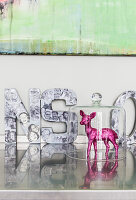 Pink, glittery fawn under glass cover and decorative letters on glossy surface