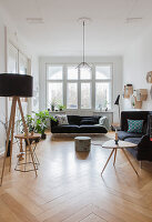 Standard lamp, sofa set, coffee table and houseplants in period apartment
