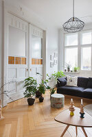Sofa and houseplants in front of double doors in period apartment