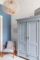 Armchair next to grey wardrobe in period apartment
