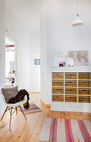 Classic chair in front of open doorway and tall chest of drawers in period apartment