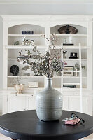 Dried flowers in stoneware vase on round table in front of shelves
