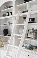 Elegant ornaments on white shelves with library ladder