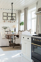 Elegant country-house kitchen-dining room with white wooden floor