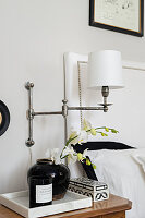 Articulated wall-mounted lamp above black and white ornaments on bedside table