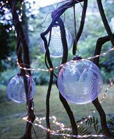 Transparent, patterned glass baubles and fairy lights hung amongst branches