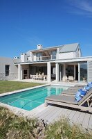 Pool and lawn outside elegant holiday home beneath blue sky