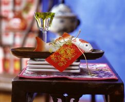 Plastic koi and Japanese tag on wooden tray