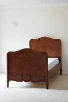Antique bed with wooden veneer, headboard and foot