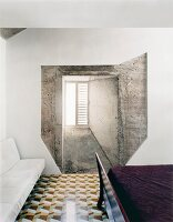 Unusual composition of window in concrete wall in bedroom with geometric floor tiles