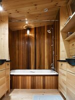 White bathtub with wooden cladding and fitted washstands and cupboards