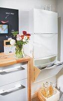 Wertstoffcenter in der Küche, Kunststoffbox für Papier, Holzkiste für Altglas, weisse Küchenzeile mit Holzarbeitsfläche und Ranunkelstrauss