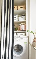 A utility room with washing machine behind a striped curtain