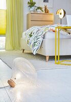 A floor light in a bedroom with a double bed and a yellow bedside table
