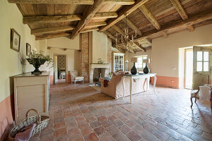 Terracotta floor and exposed roof structure in Mediterranean living room