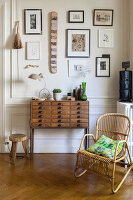 Rattan chair and chest of small drawers below gallery of pictures on wall