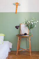 Round, rattan bedside table against two-tone painted wall