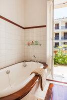 Bathtub with wooden rim next to open balcony door