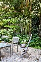 Weathered garden furniture on gravel terrace in wild garden