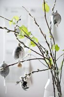 Marbled Easter eggs hung from willow and beech branches in vase