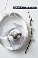 Marmoriertes Osterei neben Zweig mit Weidenkätzchen und Etikett
