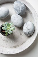 Easter eggs painted with stone effects in concrete bowl
