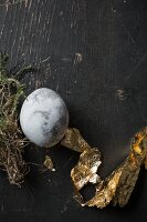 Easter egg painted with stone effect and gold leaf on black-painted wood