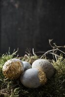 Easter eggs painted with stone effects and gold leaf on moss