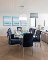 Blue upholstered chairs around dining table in front of seascape paintings on wall in open-plan interior