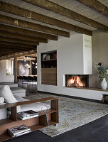 Fireplace and rustic wooden ceiling beams in elegant lounge