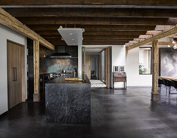 Custom kitchen island made from black marble in open-plan interior with concrete floor and rustic wooden ceiling beams