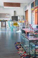 Großer Wohnraum mit Sofa, Esstisch und offener Küche